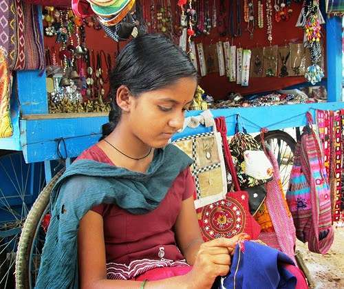 A young girl doing embroidery on a bag for selling it at her stall in Hampi, Karnataka
