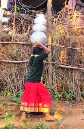 Carrying loads of water from community hand-pump for her house in Dumbriguda, Andhra Pradesh