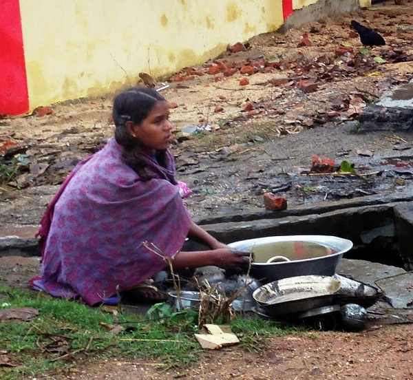 Washing utensils with cold water in winters and then carrying it home in Shivrajpur, Jharkhand